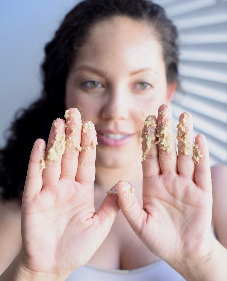 Scrub viso pelle grassa, donna che mostra le mani con la maschera da applicare sulla pelle