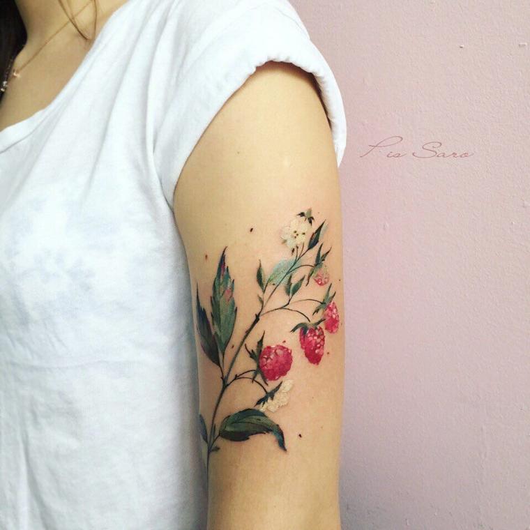 Tattoo scritte braccio, donna con un tatuaggio sul bicipite colorato con lamponi e foglie verdi