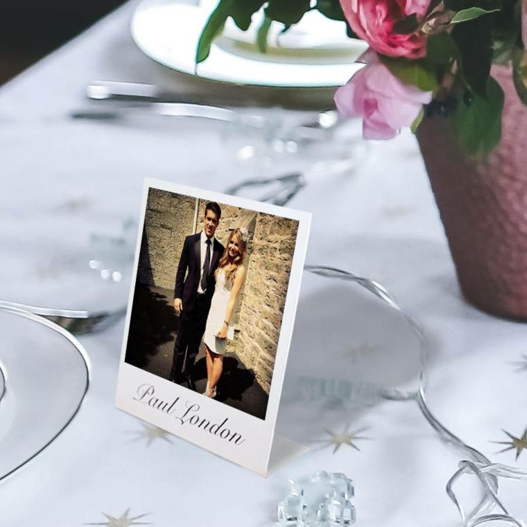 Tavolo decorato con fili luminosi e segnaposto fai da te con foto degli sposi