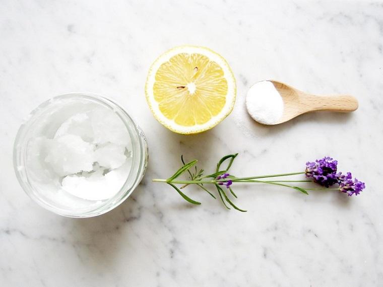 Scrub viso bicarbonato e cocco, crema in ciotola di vetro con il succo di mezzo limone e olio di lavanda
