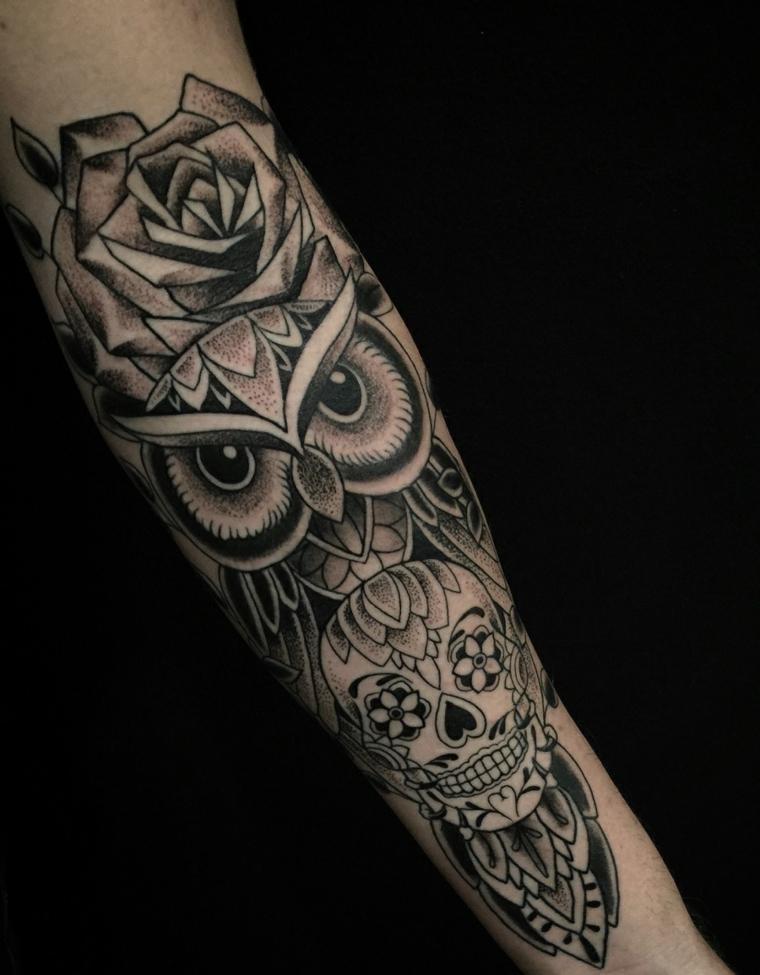 Un grande tatuaggio sull'avambraccio di un uomo con un gufo e un teschio con fiori