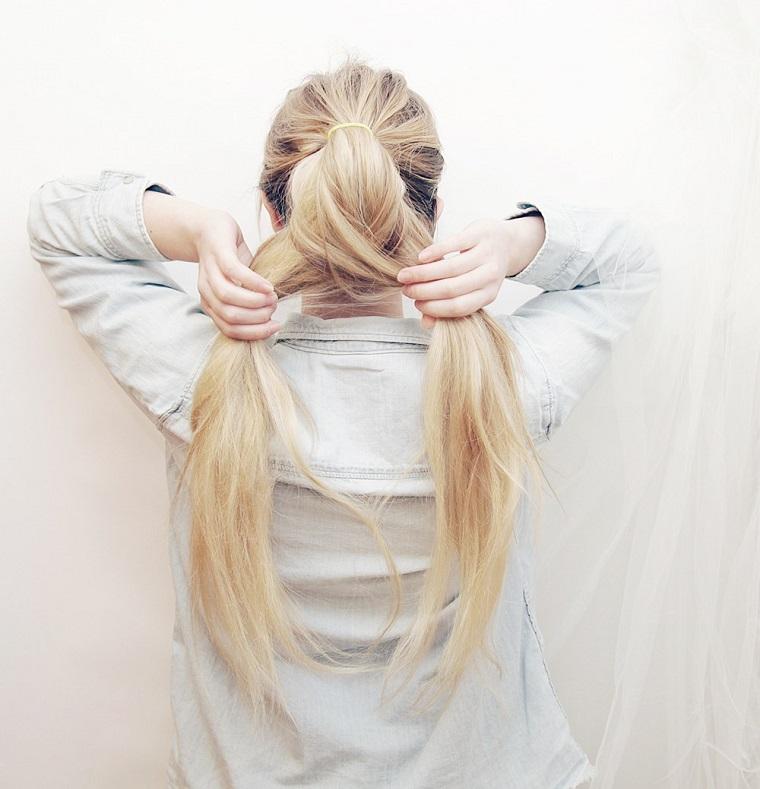 Come fare la treccia a spina di pesce di una ragazza con i capelli biondi lunghi