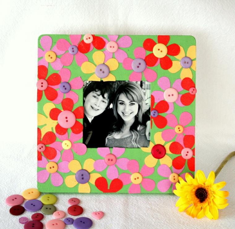Cornici foto fai da te con decorazioni, bottoni colorati incollati su dei fiorellini di carta