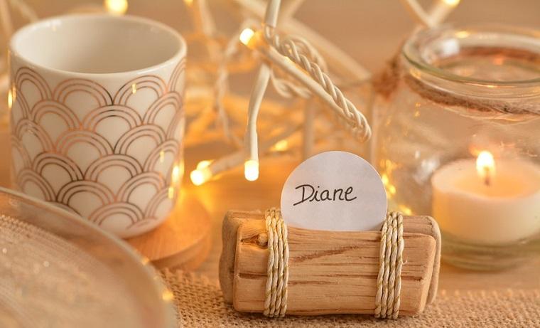 Tavolo decorato con fili luminosi e candele segnaposto, biglietto fissato su un pezzo di legno