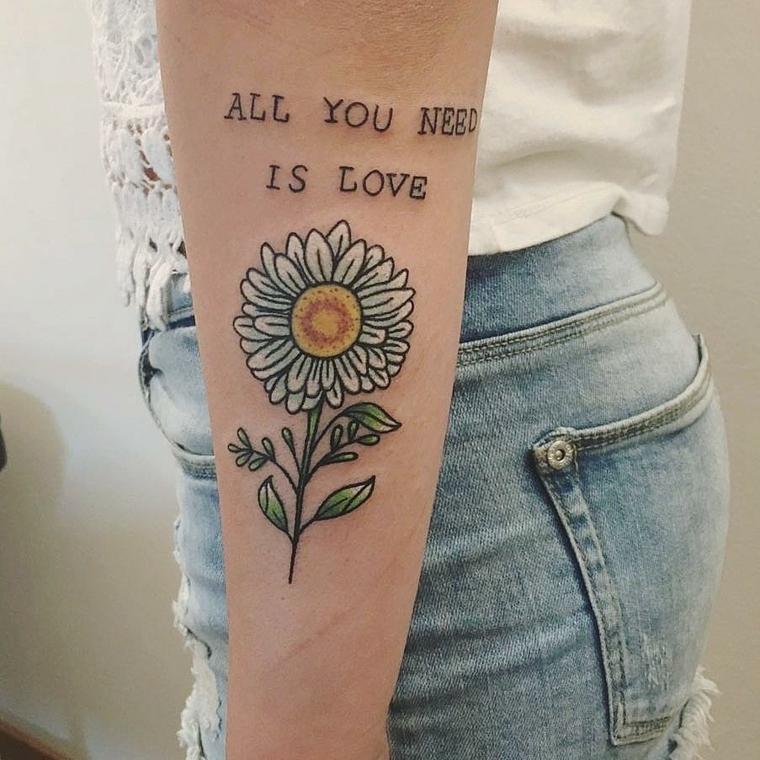 Idee per dei tattoo scritte braccio con un girasole e una citazione in inglese con lette maiuscole