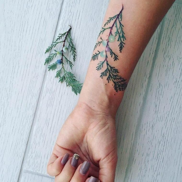 Tattoo avambraccio colorato di una donna con un disegno di rametto verde con palline