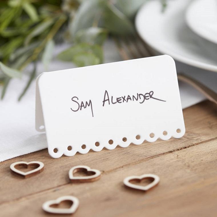 Segnaposto economici con un biglietto e il nome dell'invitato scritto, cuori di metallo su un tavolo di legno