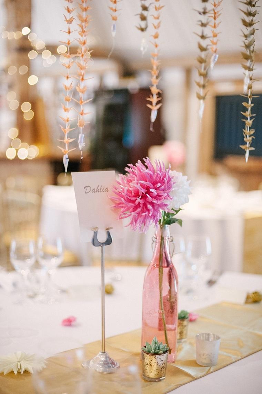 Tavolo apparecchiato con un centrotavola bottiglia di vetro rosa con fiore, candele segnaposto per un matrimonio