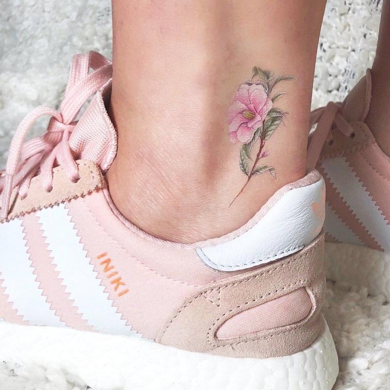Tatuaggi alla caviglia femminili con un fiore colorato, ragazza con scarpe da ginnastica rosa