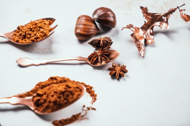 Ricetta cioccolata calda, cucchiai con cacao in polvere, tavolo con castagne