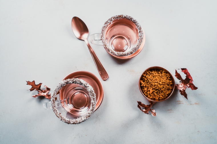Cioccolata calda, tazza di vetro con scaglie di cocco e cioccolato fondente, ciotola con cacao in polvere