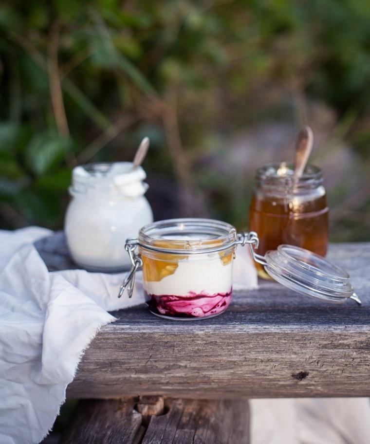 Scrub viso fatto in casa a base di yogurt greco, miele e mirtilli conservato in un barattolo di vetro