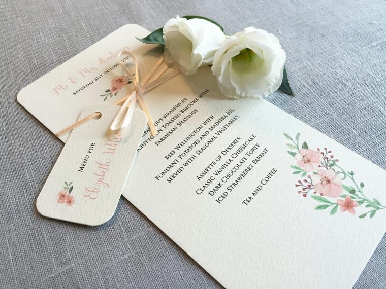 Foglio con il menu matrimonio come segnaposto decorato con due rose bianche