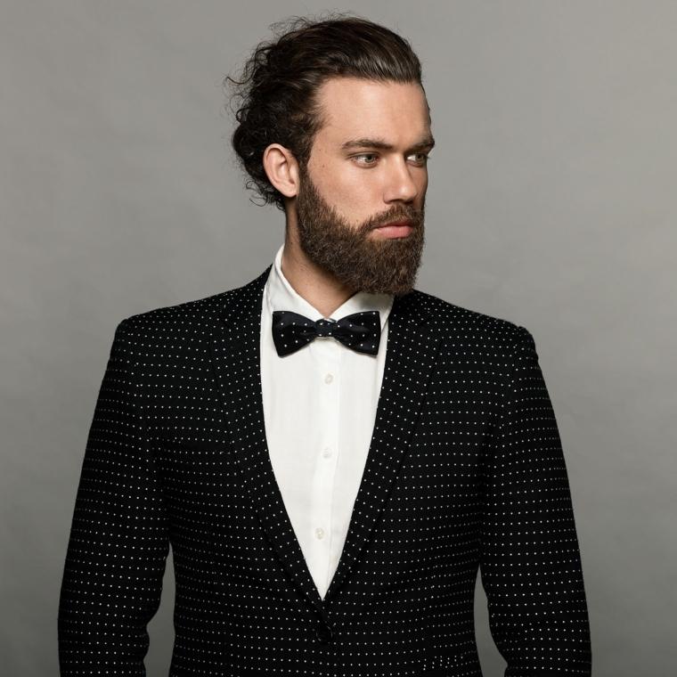 Uomo con capelli ricci legati e barba folta e corta, vestito elegante con giacca a pois