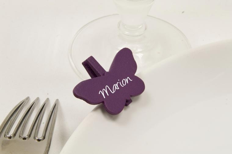 Idea fai da te per un segnaposto con molletta di legno di colore viola fissata al tavolo nuziale