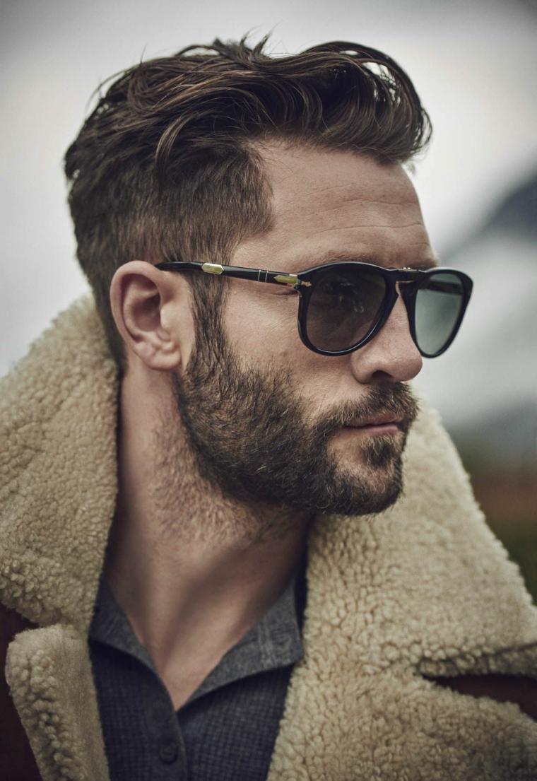 Ragazzo con occhiali da vista e acconciatura capelli rasati ai lati, barba folta con baffetti