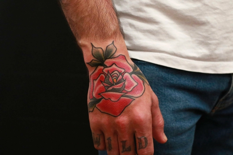 La mano di un uomo con una rosa rosa old school e la scritta wild sulle dita