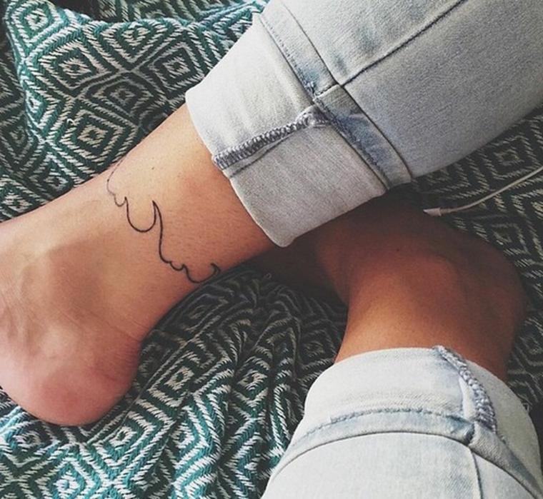 Tattoo caviglia di una donna con i jeans, tatuaggio onda del mare tipo braccialetto