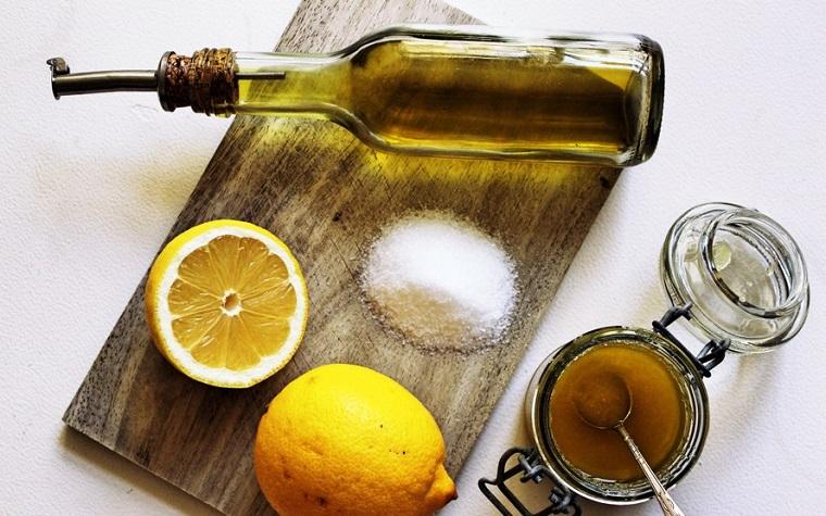 Ingredienti per preparare uno scrub a base di olio extravergine d'oliva, succo di limone e zucchero