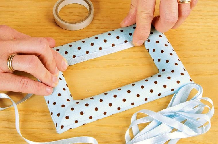Portafoto in legno rivestita con della stoffa azzurra a pois e bordi con del nastro