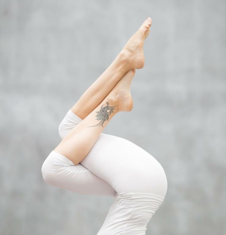 Tatuaggi sul piede femminile, donna che fa yoga con un tattoo sulla caviglia