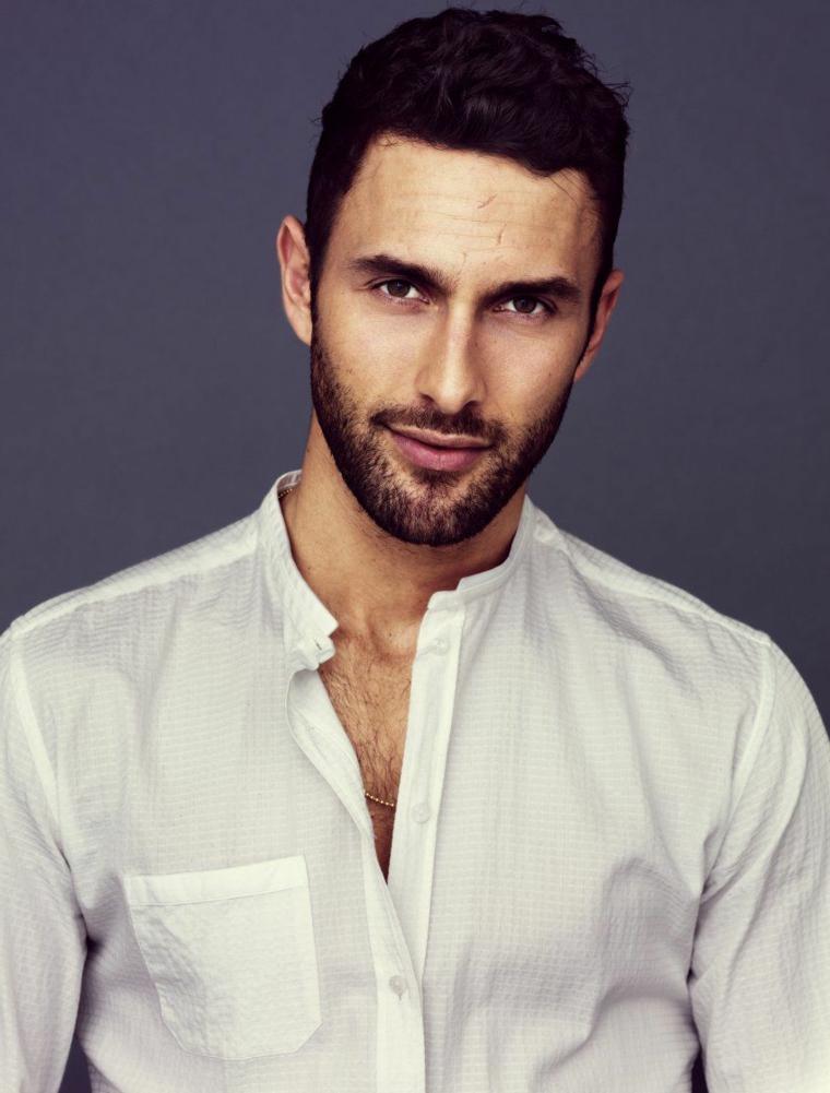 Ragazzo con capelli corti neri e cortissima barba, abbigliamento casual con una camicia bianca