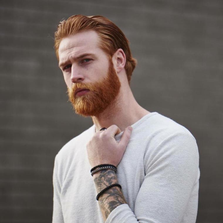 Come curare la barba, uomo con capelli rossicci e baffetti lunghi e tatuaggi sul braccio