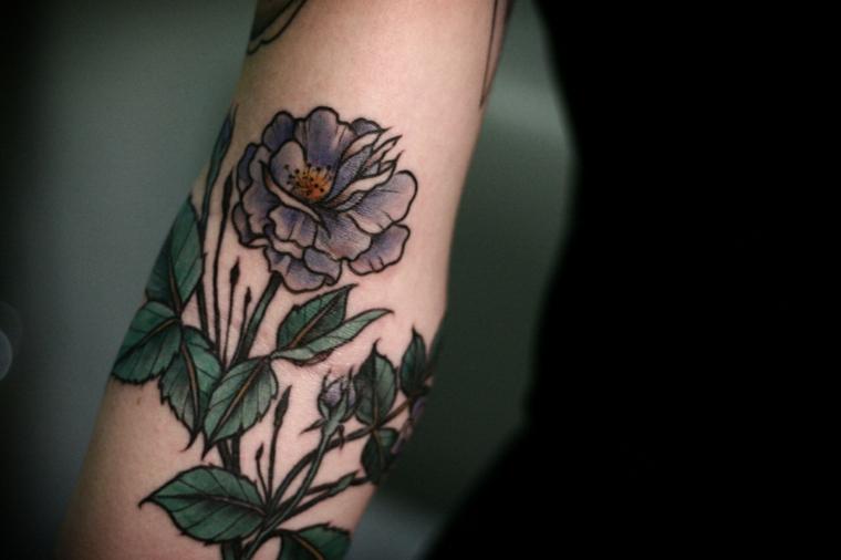 Un fiore colorato tatuato sul braccio di una donna con foglie verdi