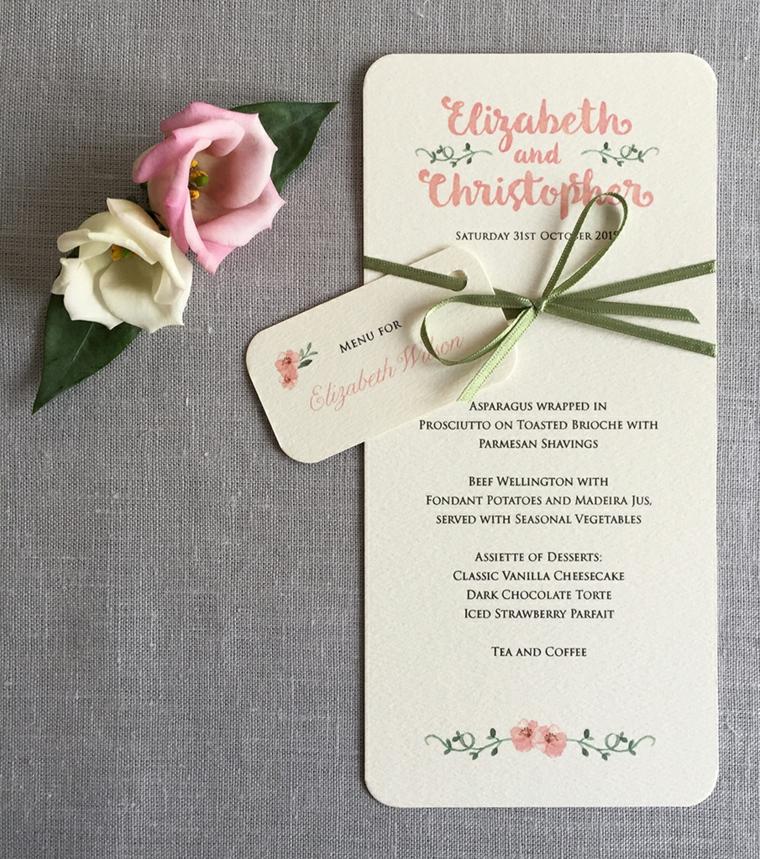 Foglio con il menu matrimonio legato con un nastro verde e decorato con rose