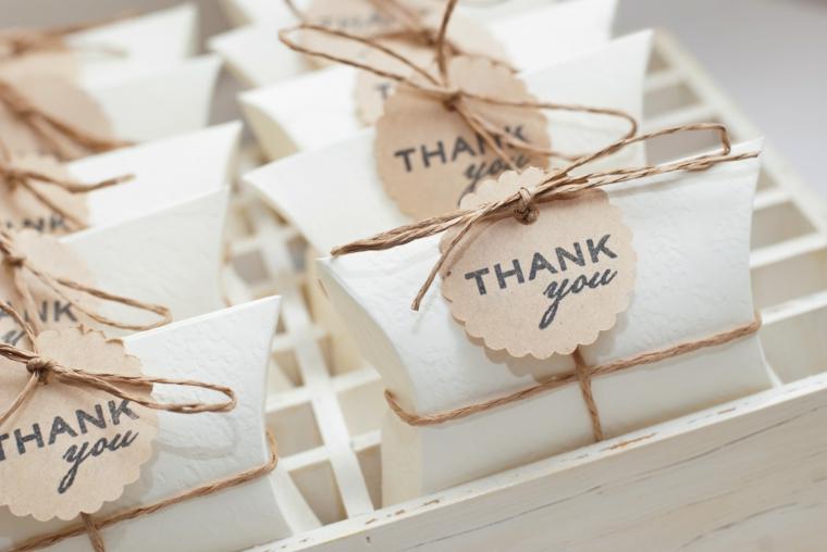 Sacchettini di carta legati con filo di canapa come segnaposto ad un tavolo nuziale