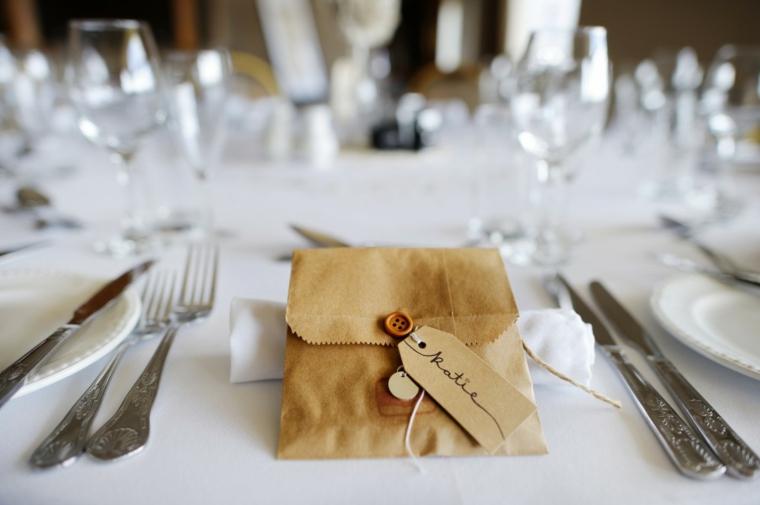 Segnaposto originali con dei sacchettini di carta su un tavolo apparecchiato