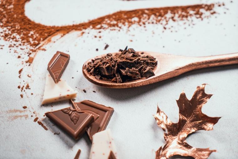 Cucchiaio di legno con scaglie di cioccolato fondente, cioccolata calda, polvere di cacao