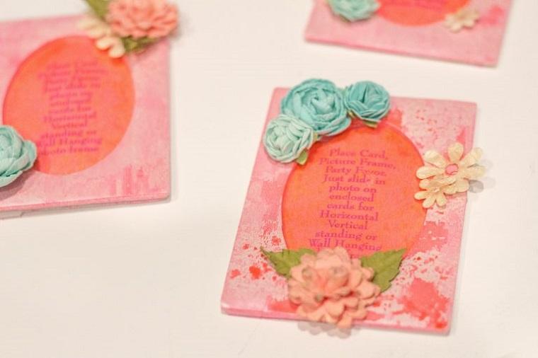Segnaposto fai da te con una cartolina decorata con fiori finti di diverso colore
