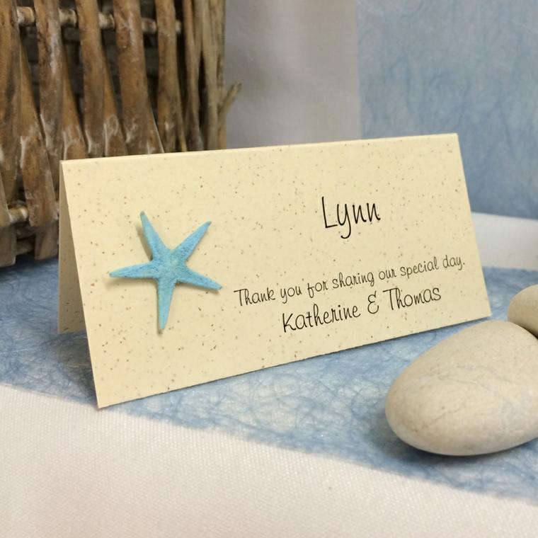 Cartolina con stella marina fissata e sassi decorativi, tavolo nuziale con segnaposto
