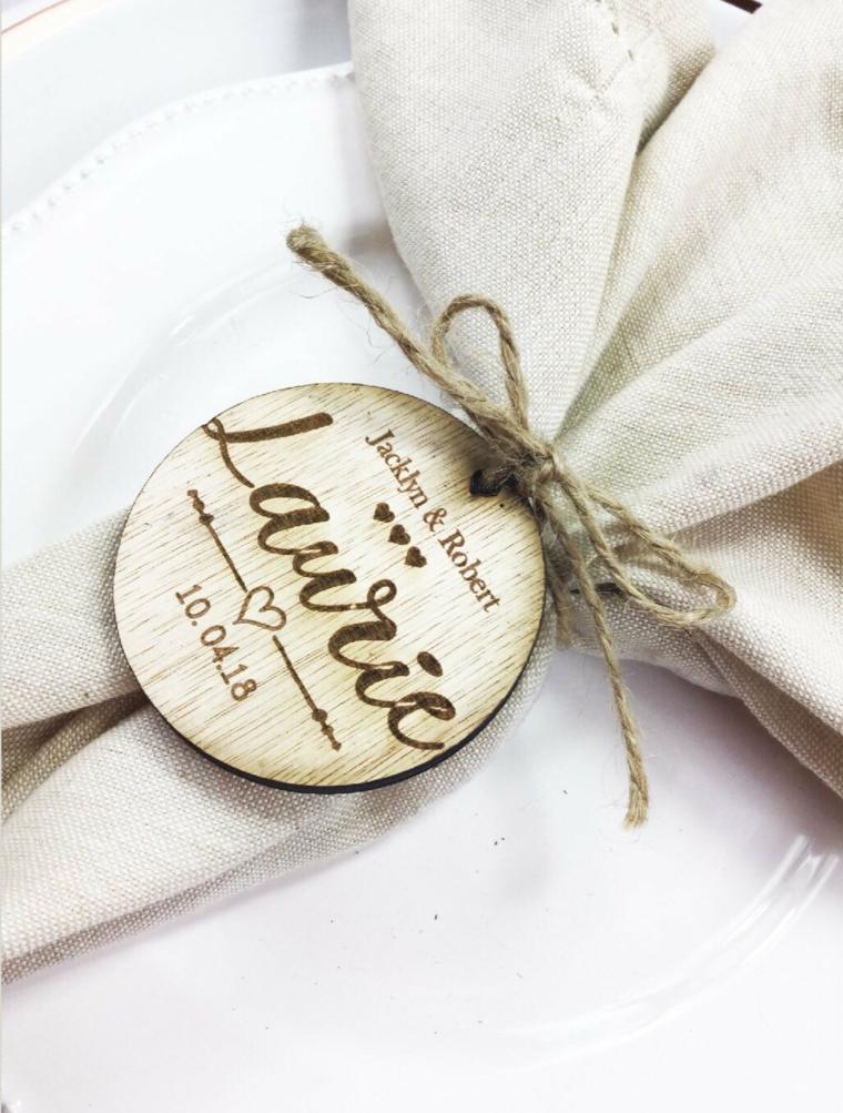 Tovagliolo legato con filo di canapa e un segnaposto rotondo di legno con il nome dell'invitato inciso