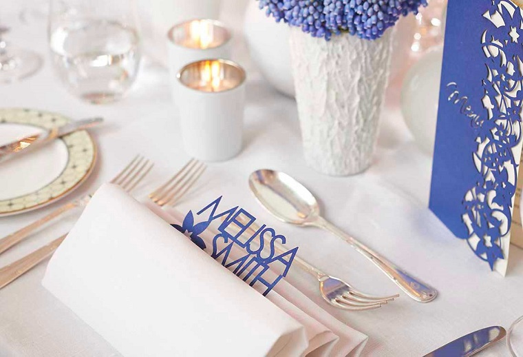 Idee con candele segnaposto e tovagliolo con il nome degli invitati con lettere di colore blu