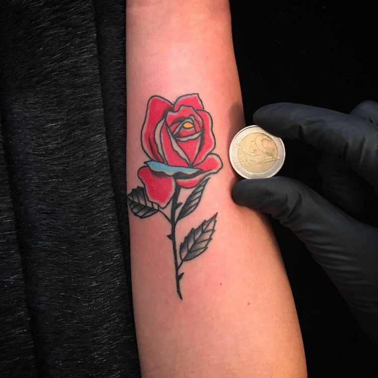 Idee per dei tatuaggi femminili braccio, disegno di una rosa rossa per paragonare le dimensioni