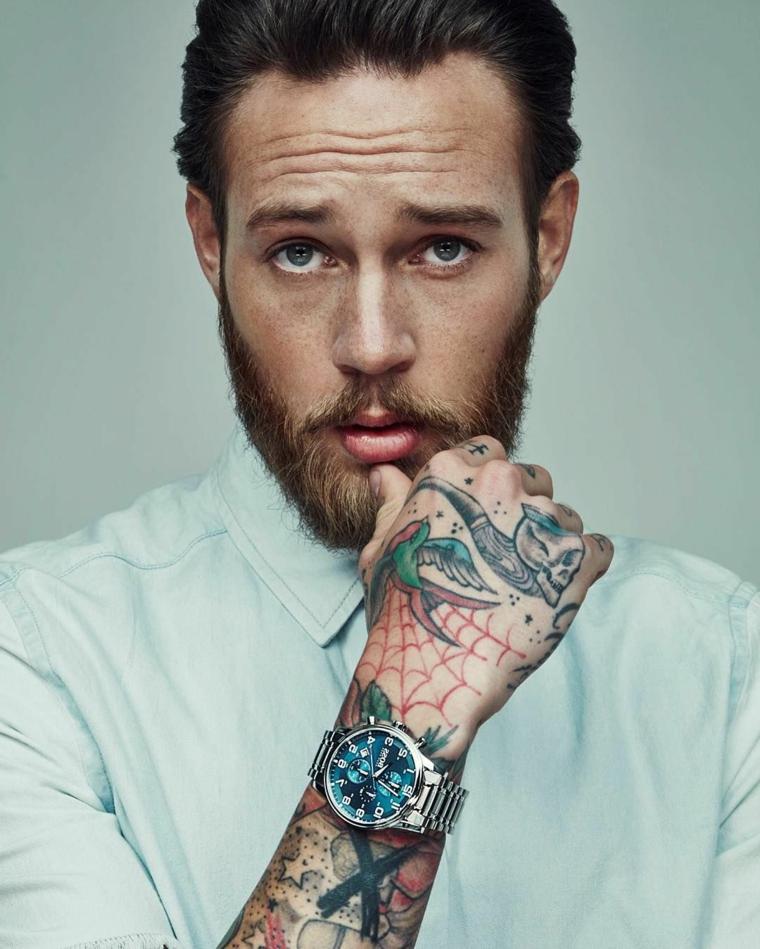 Uomo con tatuaggi sul braccio e barba leggermente lunga, capelli tirati indietro