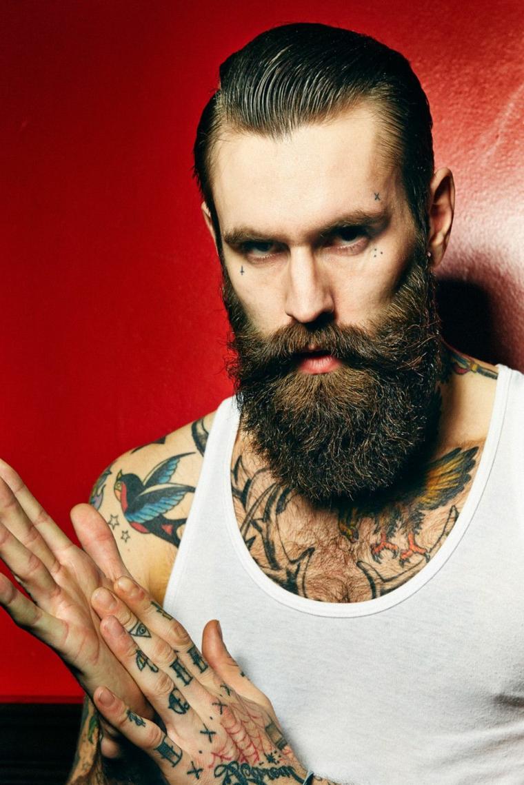 Uomo con capelli rasati ai lati e tanti tatuaggi sul corpo, barba lunga con baffi