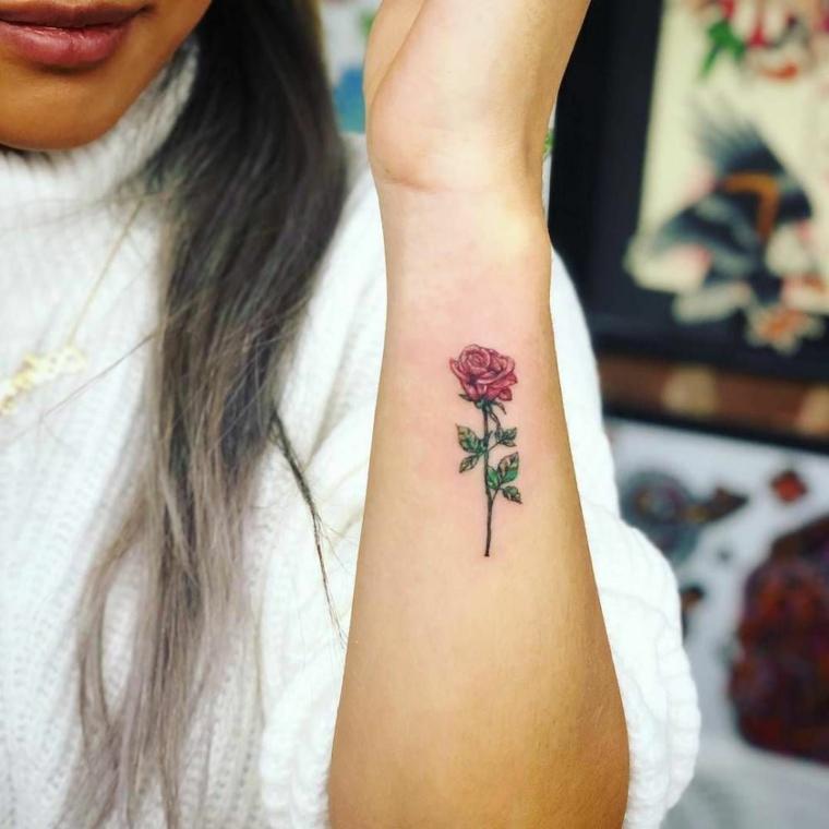 Avambraccio di una donna con un tattoo di una rosa colorata, tatuaggio bracciale piccolo