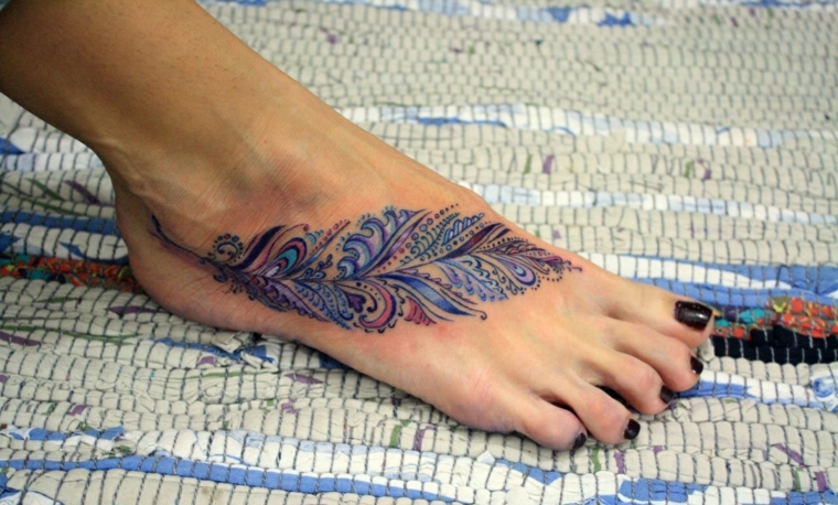 Tattoo stilizzati sulla caviglia di una donna, disegno colorato di una piuma