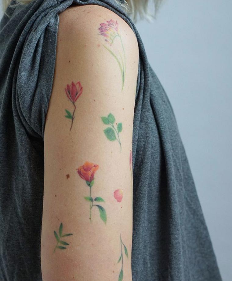 Tattoo avambraccio con disegni di tanti fiori colorati a distanza anche sul bicipite
