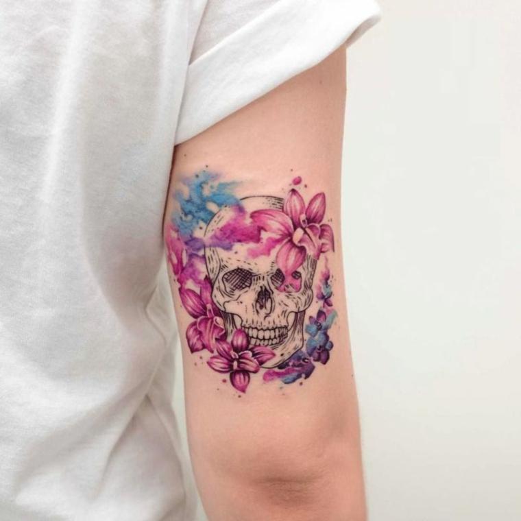 Tatuaggi tutto il braccio, tatto con un teschio e tanti fiori colorati sul bicipite di una donna