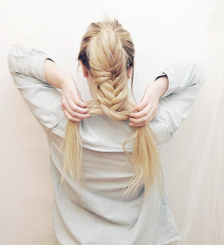 Ragazza che si fa un'acconciatura, capelli biondi con una treccia fai da te a spiga