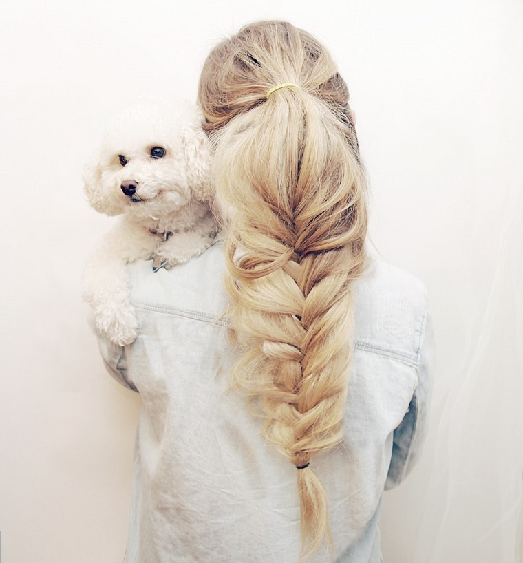 Ragazza con i capelli biondi e acconciatura treccia a spiga con cane piccolo tra le braccia