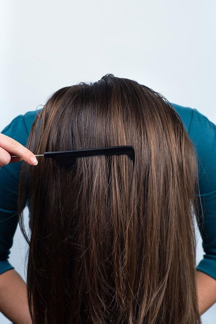 Donna con la testa all'ingiù che si spazzola, idea per fare una treccia francese particolare