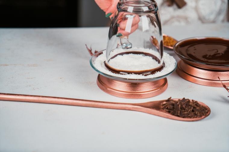Immergere tazza di vetro nelle scaglie di cocco, cioccolata calda, cucchiaio con scaglie di cioccolato