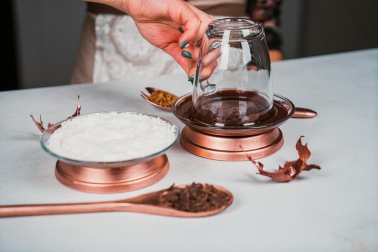 Dolci veloci senza cottura, tazza di vetro immersa nella cioccolata, piattino con scaglie di cocco