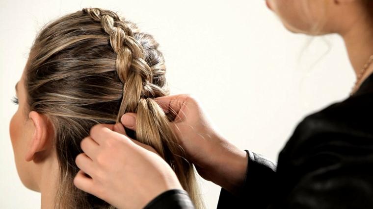 Donna che fa una treccia attaccata alla testa in stile francese, capelli castani con colpi di sole