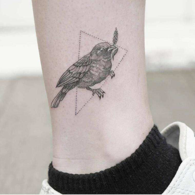 Uomo con un tatuaggio sulla caviglia di un uccello con puntini in u triangolo